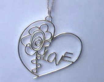 A sterling silver pendant from two childrens drawings