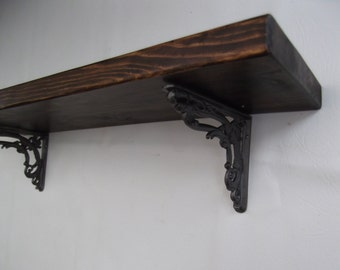 Rustic shelf handmade from reclaimed timber with 2 repro victorian cast iron brackets. Finished in briwax tudor oak . 600 x 225 x 35mm