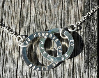 The purpose of our lives is to be happy. Double circle silver necklace stamped with inspirational quote.