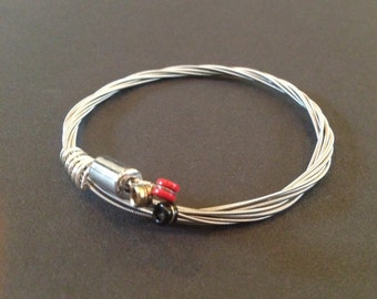 A handmade 3 string recycled guitar string bracelet/bangle with a silver coloured tube and bound with silver coloured wire.