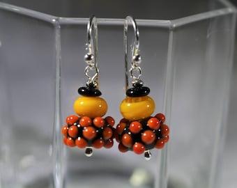 Black lampwork bead with orange raised dots