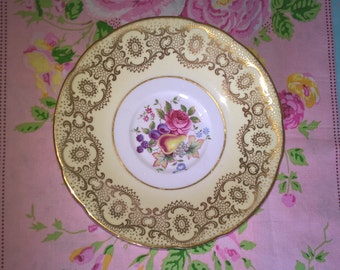 Paragon saucer with elaborately gilded lemon border and fruit and flowers in the centre. Would mix and match or use a trinket dish.