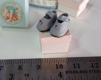 Miniature baby shoes. Dollhouse baby room