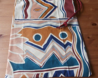 Abstract print drawstring bag with burgandy ties.