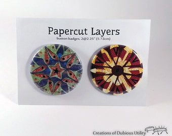 Papercut layers pair of pin back button badges