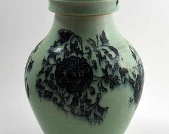 Memorial urn. Turquoise porcelain funerary urn with black floral imagery