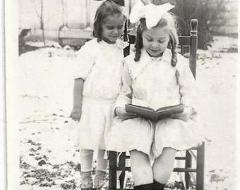 Old Photo 2 Girls wearing White Dresses and Hair Bows looking at Book outside in Snow 1910s Photograph snapshot vintage