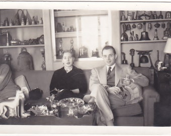 Antique Snapshot photo of a Couple Sitting on a Couch With Intresting Collection Behind Them.
