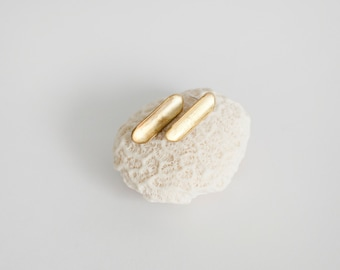 Stud earrings in brass with soft curving volume reflecting light nicely. Ear stud is in silver