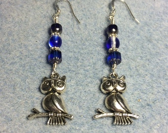 Silver owl charm dangle earrings  adorned with bright blue Czech glass beads.