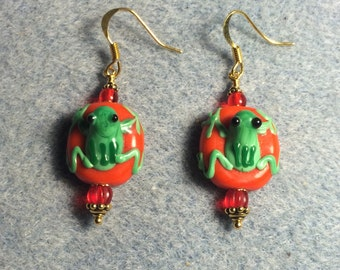 Red and green lampwork frog bead earrings adorned with red Czech glass beads.