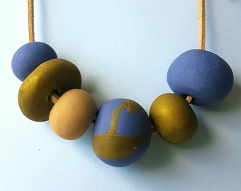 Handmade purple and gold polymer clay bead necklace.