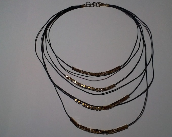 Necklace made of black leather cord & square gold colored hematite beads