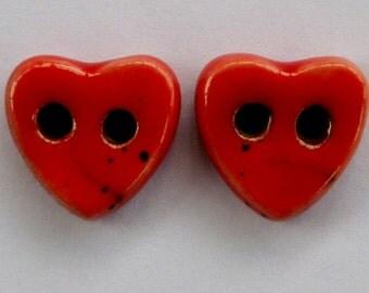 A pair of handmade red raku buttons