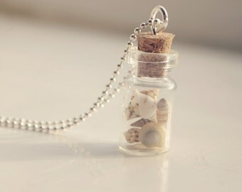 glass vial necklace filled with tiny seashells