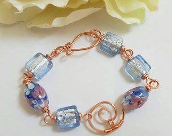 Copper wire worked bracelet, with glass flower lamp work beads and blue foil beads