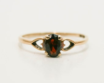 Oval garnet set in yellow gold heart ring size 7