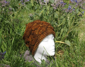 Gold hat with cables knitted hand