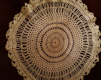 Circular crotchet doilie. It is light pink in color. It is 12 inches in diameter.