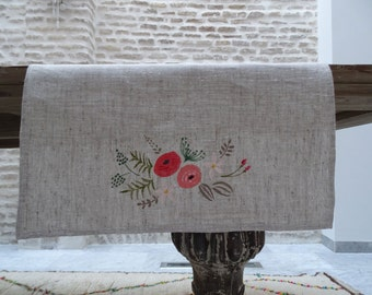 In hand-painted linen table runner. Floral motif. Available in three colors