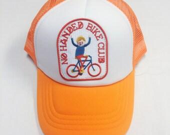 "Toddler/Kids Trucker Hat- Bright Orange with ""No Handed Bike Club"" patch"