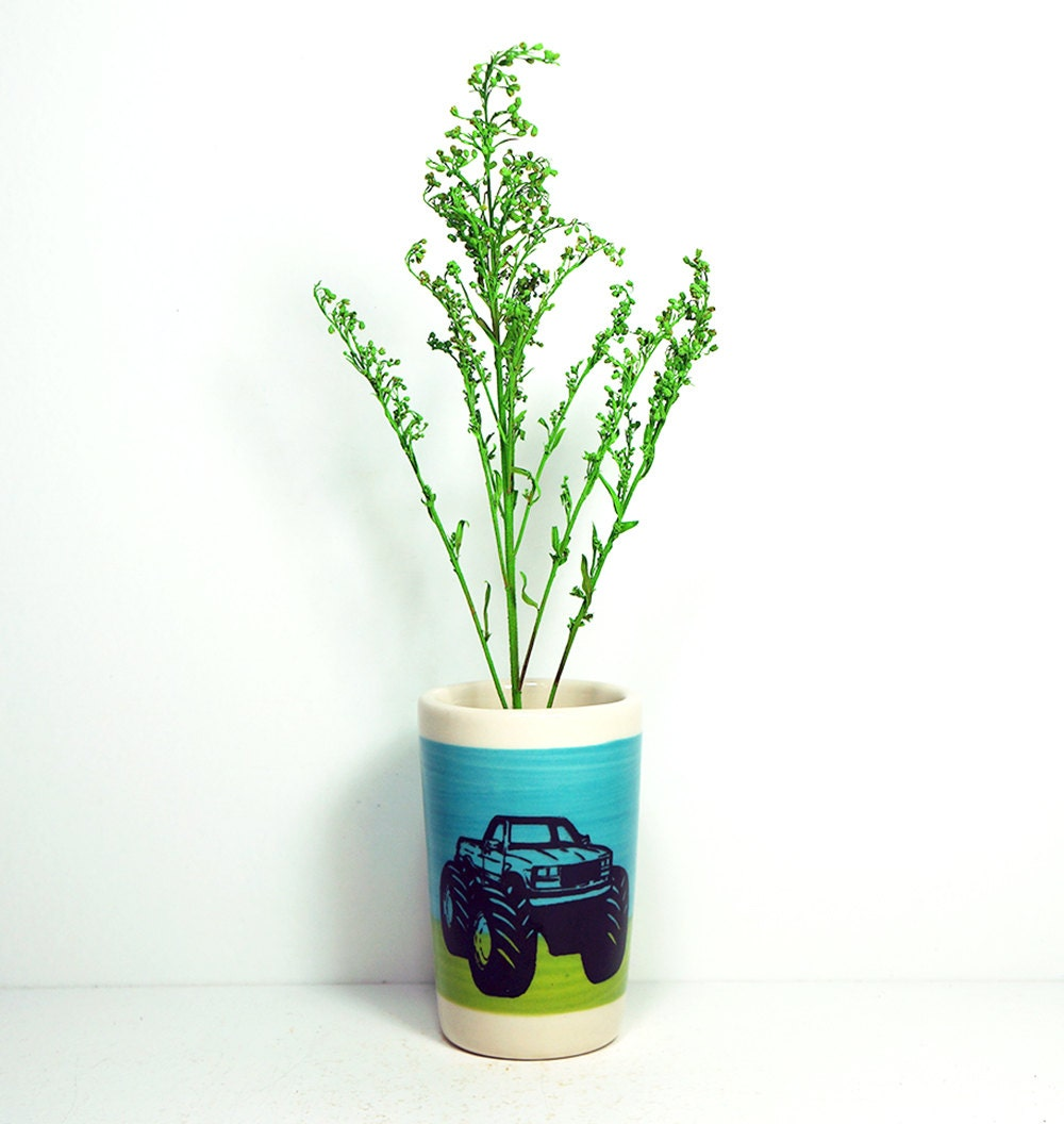 itty bitty cylinder/vase/cup in colour block of turquoise blue and leafy green, with a monster truck on it, made to order