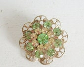 Valentines Day Sale Vintage rhinestone filigree brooch or pin green and gold round