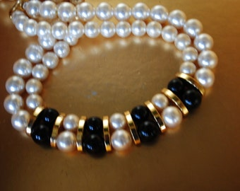 Classy vintage 80s white  and black shiny faux pearl , two stand necklace with a gold tone metal vertical bars. Made by Napier.
