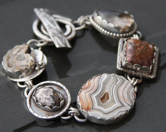 fossil shell, nickelite, crazy lace agate, copper agate, rutilated quartz, and sterling silver metalwork bracelet