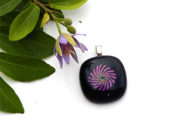 Fused glass pendant in black with a purple pinwheel in sparkly dichroic glass