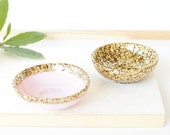 Pair of two small resin salt and pepper spice pinch trinket dish bowls in pale pastel pink and gold glitter sparkle.