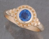 Round blue Sapphire in 14 karat yellow gold ring.