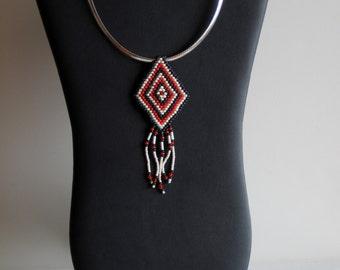 Native American beaded pendant in dark green, orange, and cream with orange crystals