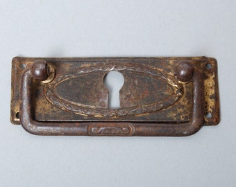 Antique key hole escutcheon with drawer pull handle.