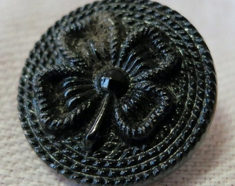 """2 Sm. black glass buttons, 4 leaf clover design set in coiled rope style rim, self shank, raised design. 0.75""""ins across. CLAM15.3-3.21-48."""