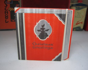 1930's art deco die cut silver gilded red and black book dsaped christmas card with silhouette of victorian dressed lady,red poinsettia