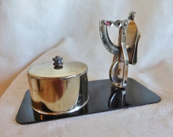 Stamp dispenser and small mechanical scale for weighing letters on black enameled metal base