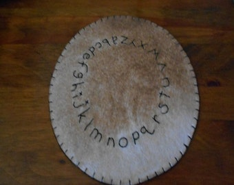 Alphabet candle mat measuring 8 inches across