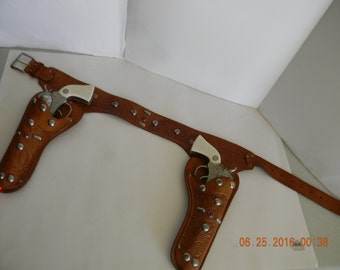 Vintage 50s Tex Tan holster set complete with Actoy cap guns in working condition