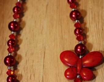 Red pearls, red crystals, silvertone spacers, red butterfly pendant, lobster claw clasp 18.5""