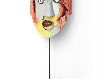 Decorative mask mounted on a metal base.