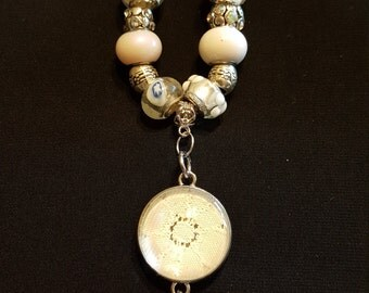 Flower pendant on white suede with white and flower beads