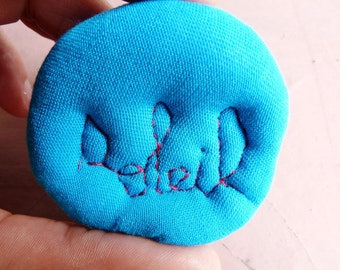 "Textile brooch with embroidered French word ""soleil"" (sun)"