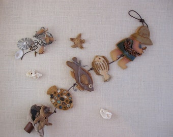 Seashore-Themed Wall Hanging - Ceramic String with 5 items -Beachcomber Girl holding Seaweed - Three Fish - Starfish on Driftwood - Mobile