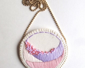 Geometric textile necklace hand embroidered in pastel pinks and lavender with glass beads on bright cream muslin and matte gold ball chain