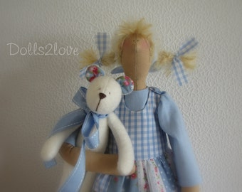 Tilda doll Audry wearing a soft blue patchwork pinafore dress accompanied by her little teddy bear