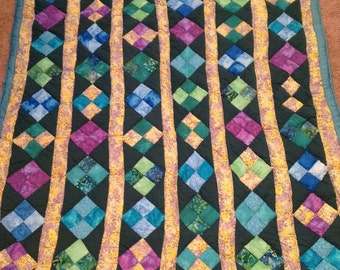 Shades of Monet. Beautiful handmade patchwork quilt with diamond patterns in greens and blues bordered in yellow pattern fabric.