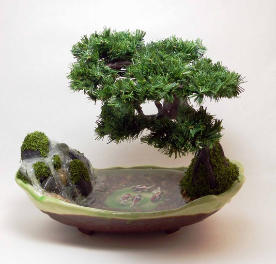 Artificial koi pond with waterfall beneath a pine bonsai for Artificial koi fish for ponds