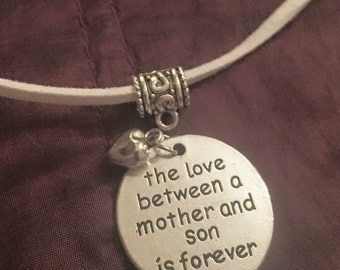 Love between a mother and son silver heart pendant on white suede necklace