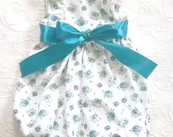 White serje baby romper with ocean/turquoise blue flowers